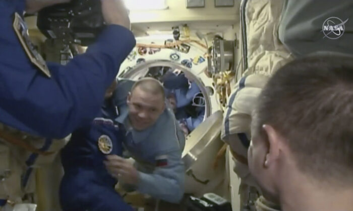 In this image from video made available by NASA, International Space Station crew members welcome cosmonauts Ivan Vagner, center, Anatoly Ivanishin and astronaut Chris Cassidy, obscured, as they exit the Soyuz capsule docked to the station on Thursday, April 9, 2020. (NASA via AP)