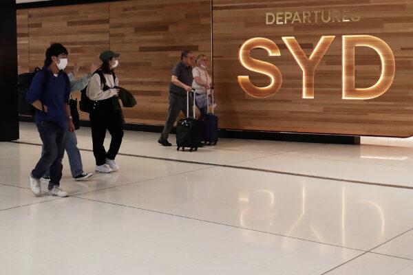 Travellers walk towards the departures gate