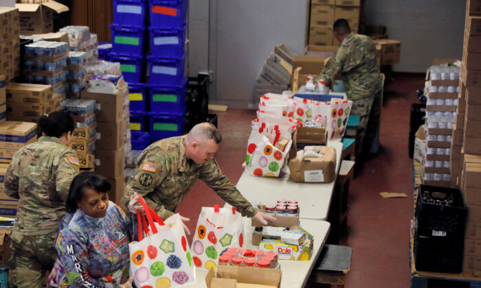 Members of the New York Army National Guard help pack pantry bags for food distribution with Hope Community Services in New Rochelle, N.Y., on March 18, 2020. (REUTERS/Andrew Kelly)