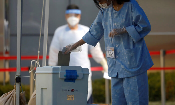 A South Korean patient affected with the CCP virus disease (COVID-19) casts her ballot for the parliamentary election at a polling station set up at a quarantine center in Yongin, South Korea, on April 11, 2020. (Kim Hong-Ji/File Photo via Reuters)