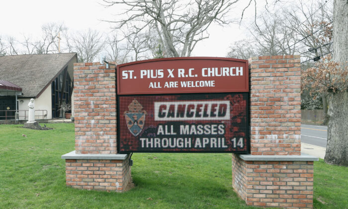 A display in front of St. Pius X R.C. Church on April 10, 2020, displays a message that all masses through April 14 are cancelled in Plainview, New York. (Bruce Bennett/Getty Images)
