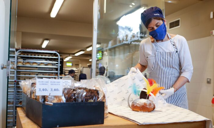An employee wearing a mask and gloves works at the Turris bakery in Barcelona, Spain, on April 11, 2020. (Pau Barrena/AFP via Getty Images)