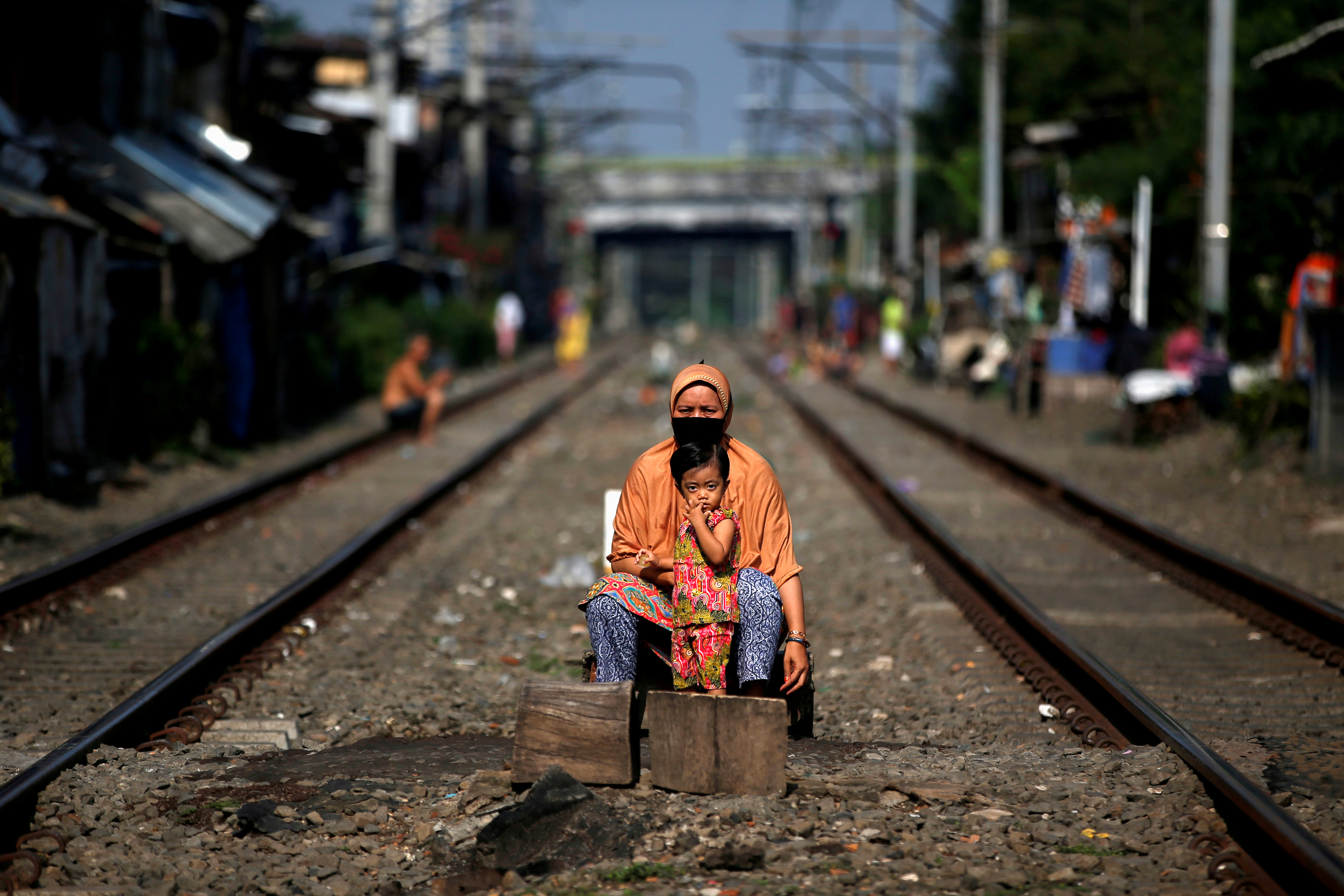 A woman and a child sit between rail tracks to enjoy sunshine as they believe it improves their immunity during social restrictions to prevent the spread of the CCP virus in Jakarta, Indonesia, on April 12, 2020. (Willy Kurniawan/Reuters)
