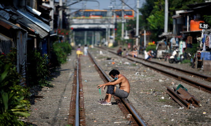 A man wears a protective mask as he sits along rail tracks during the large-scale social restrictions to prevent the spread of the CCP virus in Jakarta, Indonesia, on April 12, 2020. (Willy Kurniawan/Reuters)