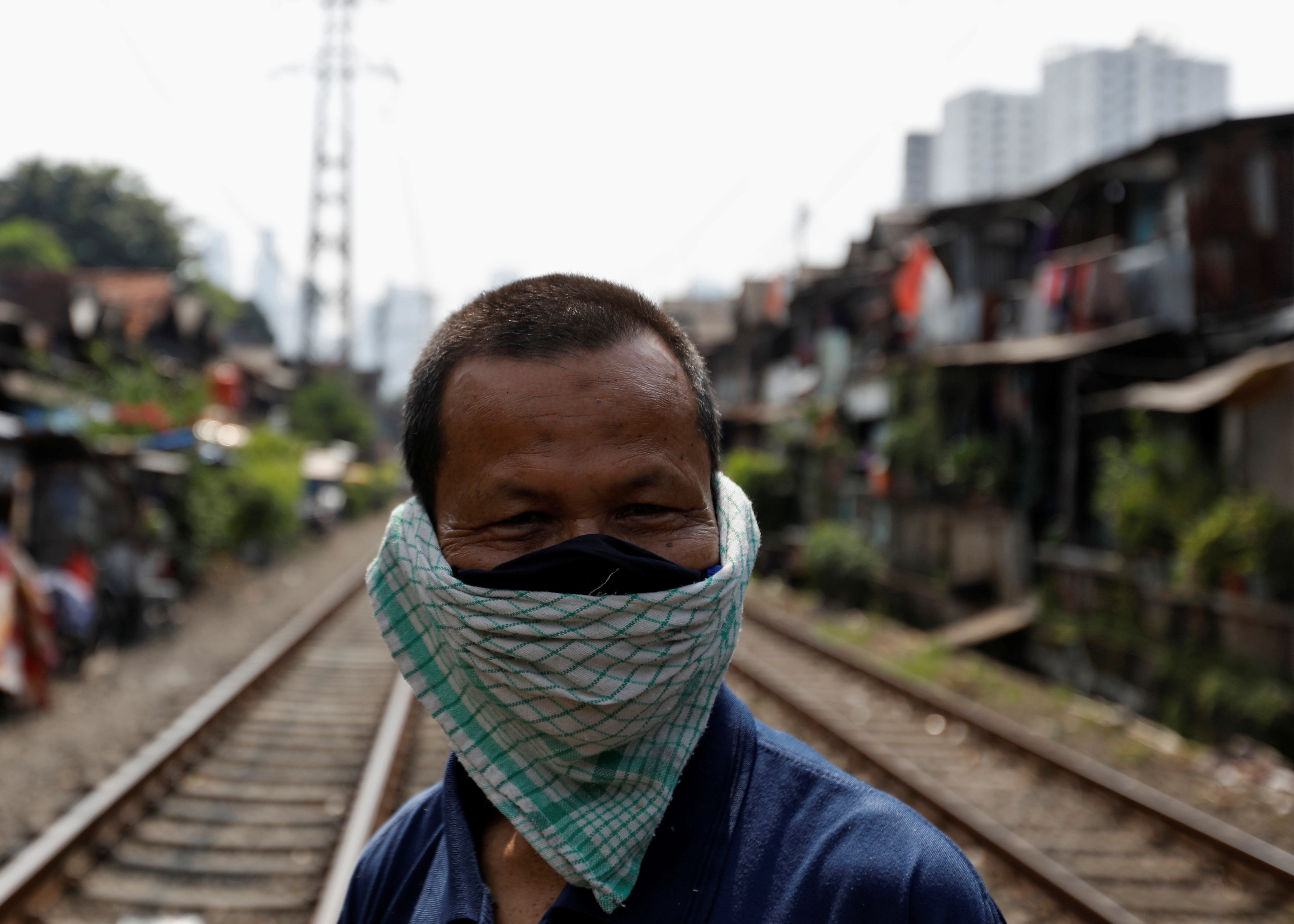 A man covers his face with a napkin along rail tracks, during the large-scale social restrictions to prevent the spread of the CCP virus in Jakarta, Indonesia, on April 12, 2020.