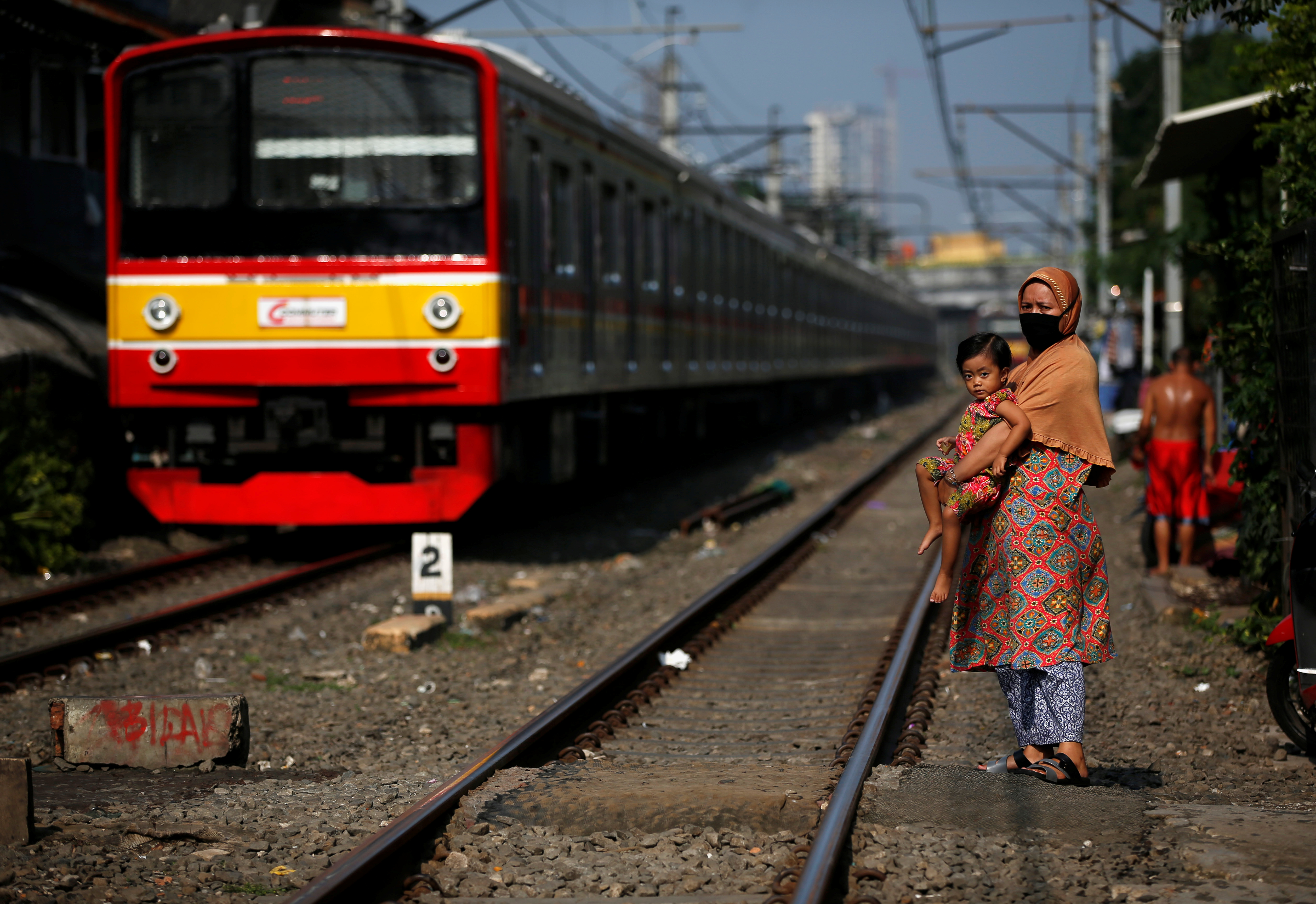A train passes next to a woman wearing a face mask and a child along rail tracks, during the large-scale social restrictions to prevent the spread of the CCP virus in Jakarta, Indonesia, on April 12, 2020.