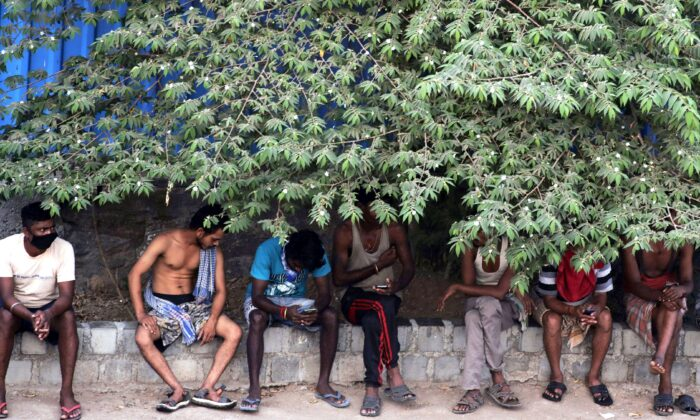 Migrant workers sit in the shade outside a slum area in Mumbai, India, on April 11, 2020. Social distancing has become the law in India, but in poor countries, observing social distancing is an option for only the better off. (AP Photo/Rajanish Kakade)