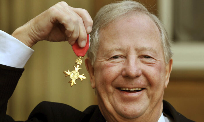 Tim Brooke-Taylor holds his OBE after being presented it by Queen Elizabeth, outside Buckingham Palace in London on Nov. 28, 2011. (John Stillwell/PA via AP)