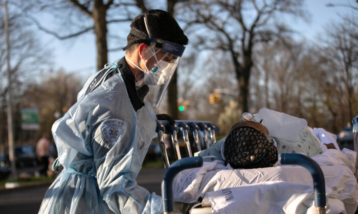 An EMT tends to a COVID-19 patient arriving at the Montefiore Medical Center Wakefield Campus in the Bronx on April 6, 2020. (John Moore/Getty Images)