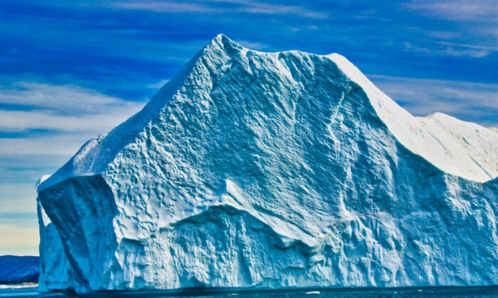 Think this iceberg is big? Often icebergs breaking from the glacier are so huge—more than 3,000 feet in height— that they're too tall to float down the fjord.  (Copyright Fred J. Eckert)