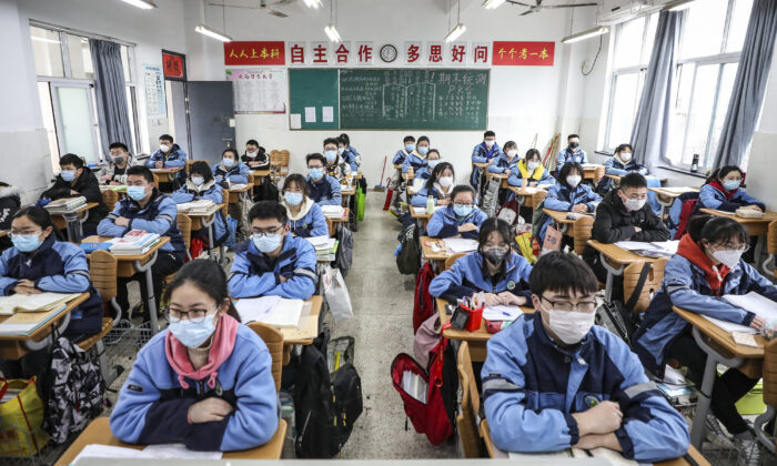 Students sit in a classroom as grade three students in middle school and high school return after the term opening was delayed due to the CCP virus outbreak in Huaian, Jiangsu province, China on March 30, 2020. (STR/AFP via Getty Images)