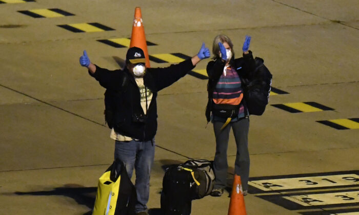 Passengers from the stranded Antarctic cruise ship, the Greg Mortimer, cleared of COVID-19 board a flight to Australia from Carrasco International Airport in Montevideo, Uruguay, on April 11, 2020. (EITAN ABRAMOVICH/Getty Images)