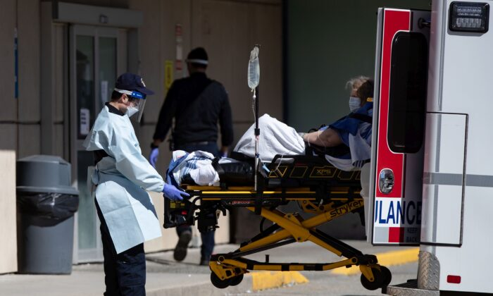 A B.C. Ambulance Service employee wearing protective gear moves a patient from an ambulance to the emergency department at Royal Columbian Hospital in New Westminster on April 12, 2020. (The Canadian Press/Darryl Dyck)