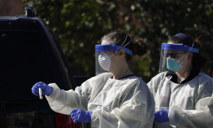 A medical professional from Children's National Hospital carries a CCP virus test specimen after administering a test at a drive-through testing site for children age 22 and under at Trinity University in Washington on April 2, 2020. (Drew Angerer/Getty Images)