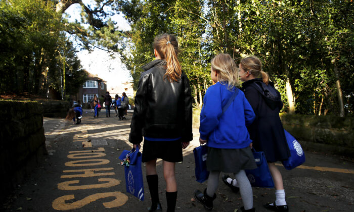 Children walk home from Altrincham C.E. aided primary school after the government's policy to close all schools from today due to the coronavirus pandemic in Altrincham, United Kingdom, on March 20, 2020. (Clive Brunskill/Getty Images)