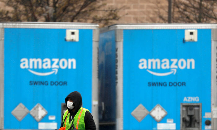 A worker in a face mask walks by trucks parked at an Amazon facility as the global CCP virus (COVID-19) outbreak continued in Bethpage on Long Island in New York, on March 17, 2020. (Andrew Kelly/File Photo/Reuters)