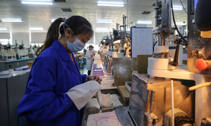 An employee is working at a photoelectric production line at a factory in Wuhan, China on April 6, 2020. (STR/AFP via Getty Images)
