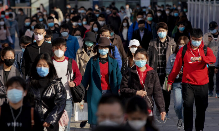Commuters wear protective masks as they exit a subway station during Monday rush hour in Beijing,on April 13, 2020. (Lintao Zhang/Getty Images)