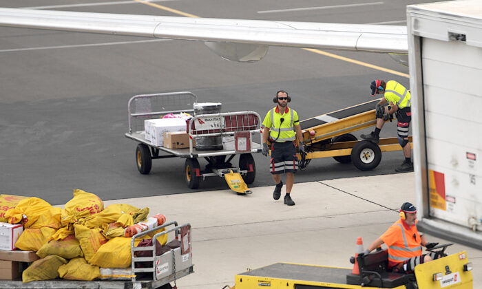 Baggage handers load a Qantas plane at Adelaide Airport in South Australia on April 1, 2020. (Tracey Nearmy/Getty Images)
