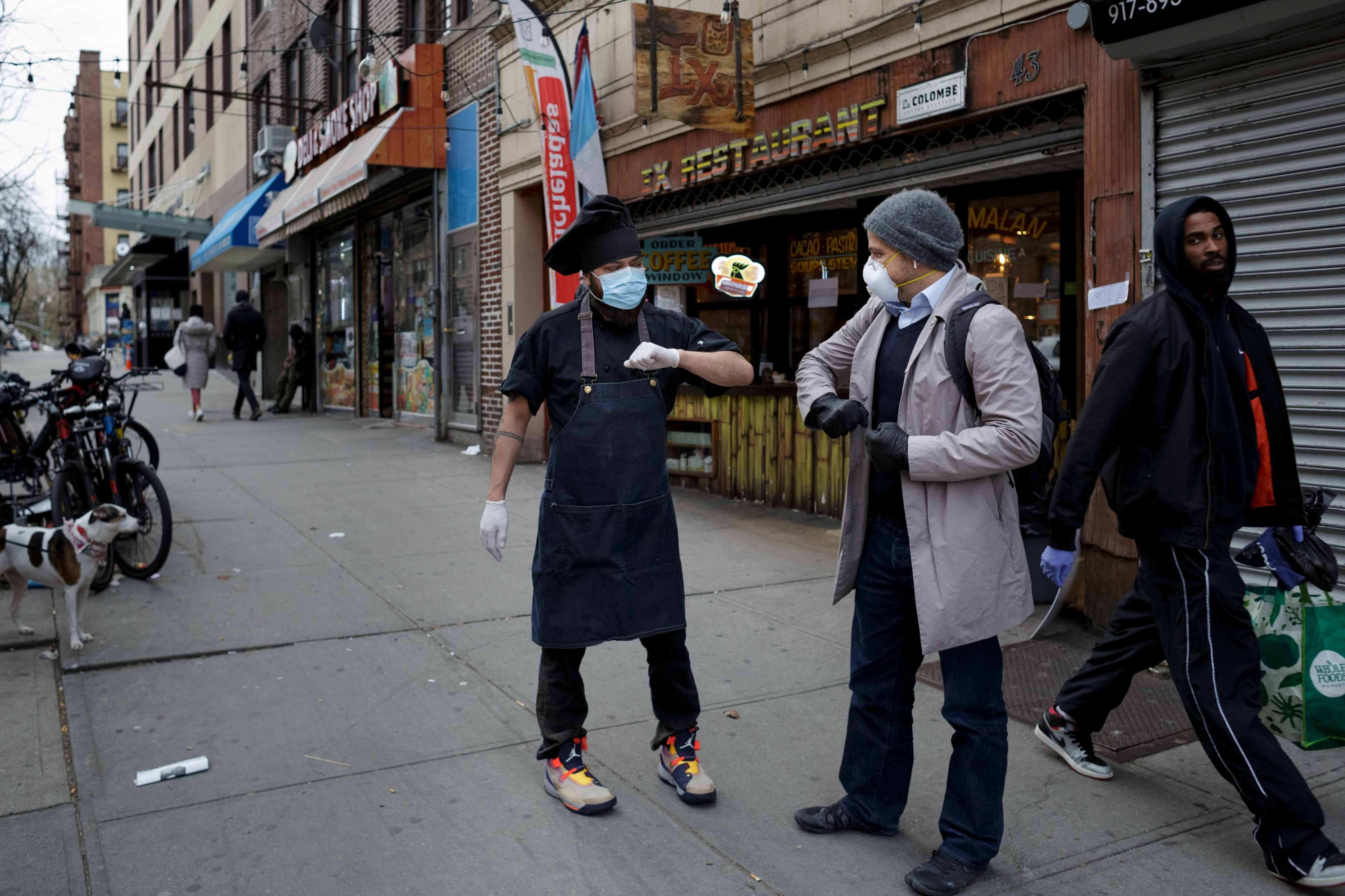Chef Jorge Cardenas shares an elbow bump with regular Ix customer Lorenzo Bernasconi outside of Ix restaurant in the Brooklyn borough of New York City, U.S., on April 2, 2020 amid the CCP virus outbreak. (Anna Watts/Reuters)