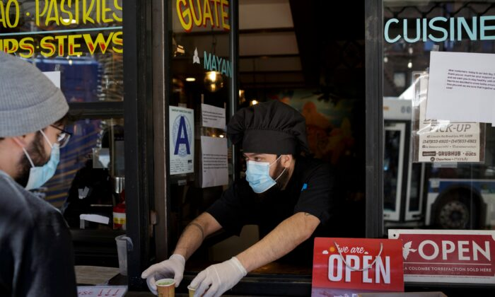 Chef and part-owner Jorge Cardenas, 41, hands customers free shots of broth while they wait for their takeout order outside of Ix restaurant in the Brooklyn borough of New York City, on April 2, 2020 amid the CCP virus outbreak. (Anna Watts/Reuters)