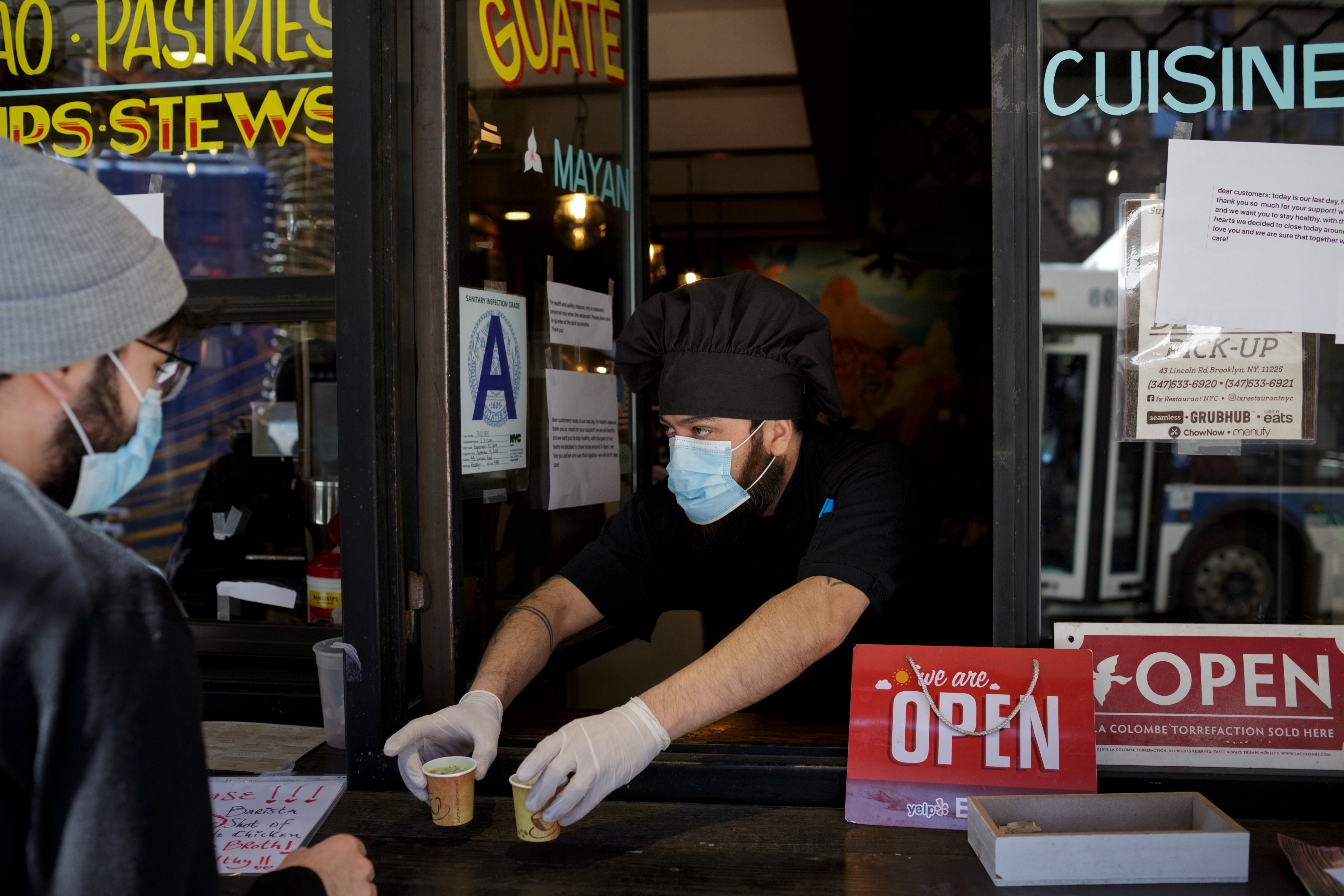 Chef and part-owner Jorge Cardenas, 41, hands customers free shots of broth while they wait for their takeout order outside of Ix restaurant in the Brooklyn borough of New York City, U.S., on April 2, 2020 amid the CCP virus outbreak. (Anna Watts/Reuters)