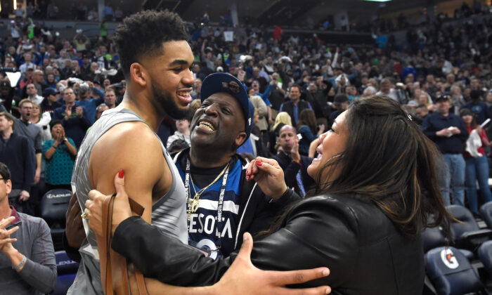 Karl-Anthony Towns of the Minnesota Timberwolves hugs his parents, Karl and Jacqueline Towns, after winning the game against the Denver Nuggets at the Target Center in Minneapolis, Minnesota, on April 11, 2018. (Hannah Foslien/Getty Images)