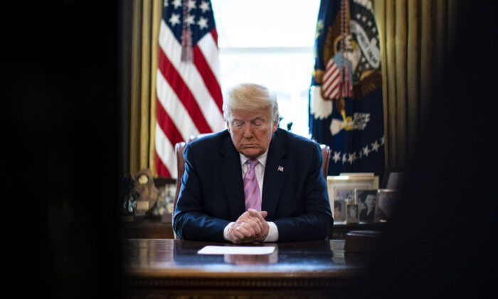 President Donald Trump bows his head during a Easter blessing by Bishop Harry Jackson, senior pastor at Hope Christian Church in Beltsville, Md., in the Oval Office of the White House in Washington, on  April 10, 2020. (Al Drago/ Pool/Getty Images)