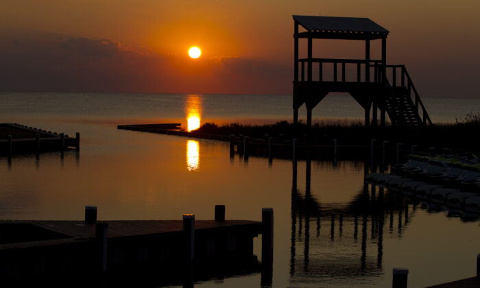A sunset as seen on the quiet waters of the Rodanthe Sound shore on the Outer Banks of Dare County, North Carolina. It is questionable whether six out-of-the-state estate owners in the region will ever see a sunset from their property any time soon after the Dare County Control Group determined that they will be banned from accessing their homes on March 20 (Jose Luis Magana/AFP/Getty Images)