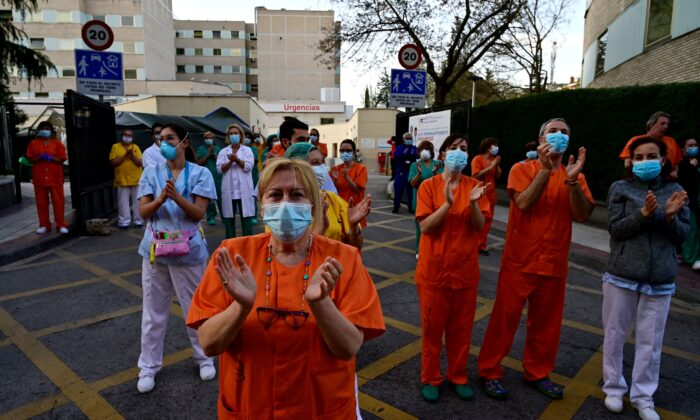 During a national lockdown to prevent the spread of the CCP virus,  healthcare workers applaud in return as they are cheered on outside the Gregorio Maranon Hospital in Madrid on April 12, 2020. (Pierre-Philippe Marcou /AFP via Getty Images)