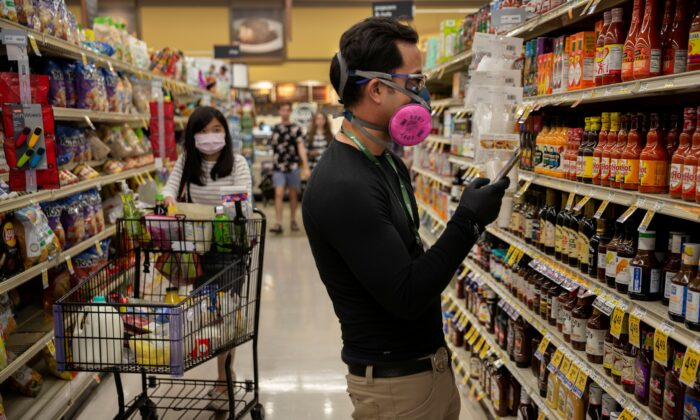 Instacart employee Eric Cohn, 34, searches for an item for a delivery order in a Safeway grocery store while wearing a respirator mask to help protect himself and slow the spread of the CCP virus disease in Tucson, Ariz., on April 4, 2020. (Cheney Orr/Reuters)