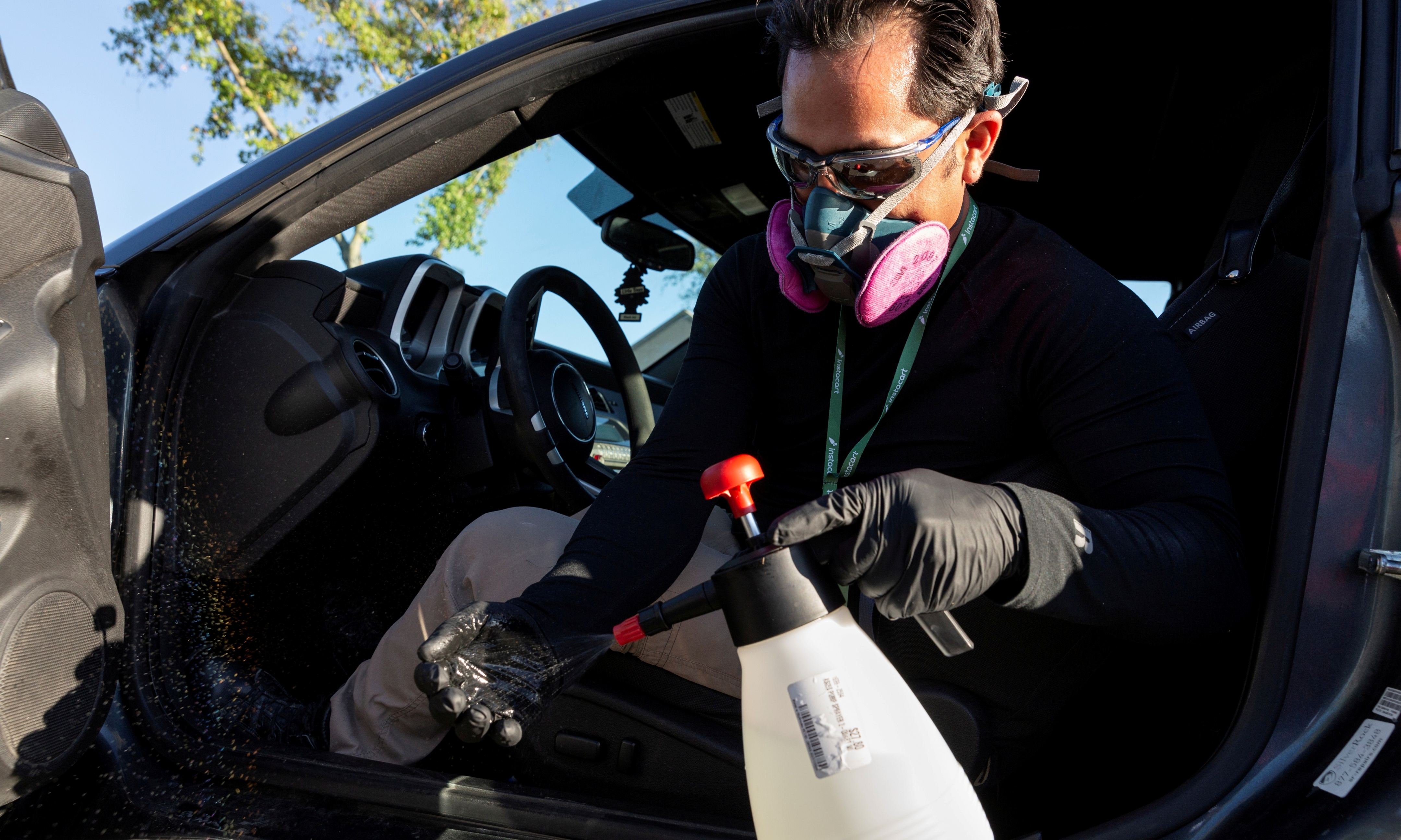 Instacart employee Eric Cohn, 34, sprays his gloves with disinfectant while wearing a respirator mask.