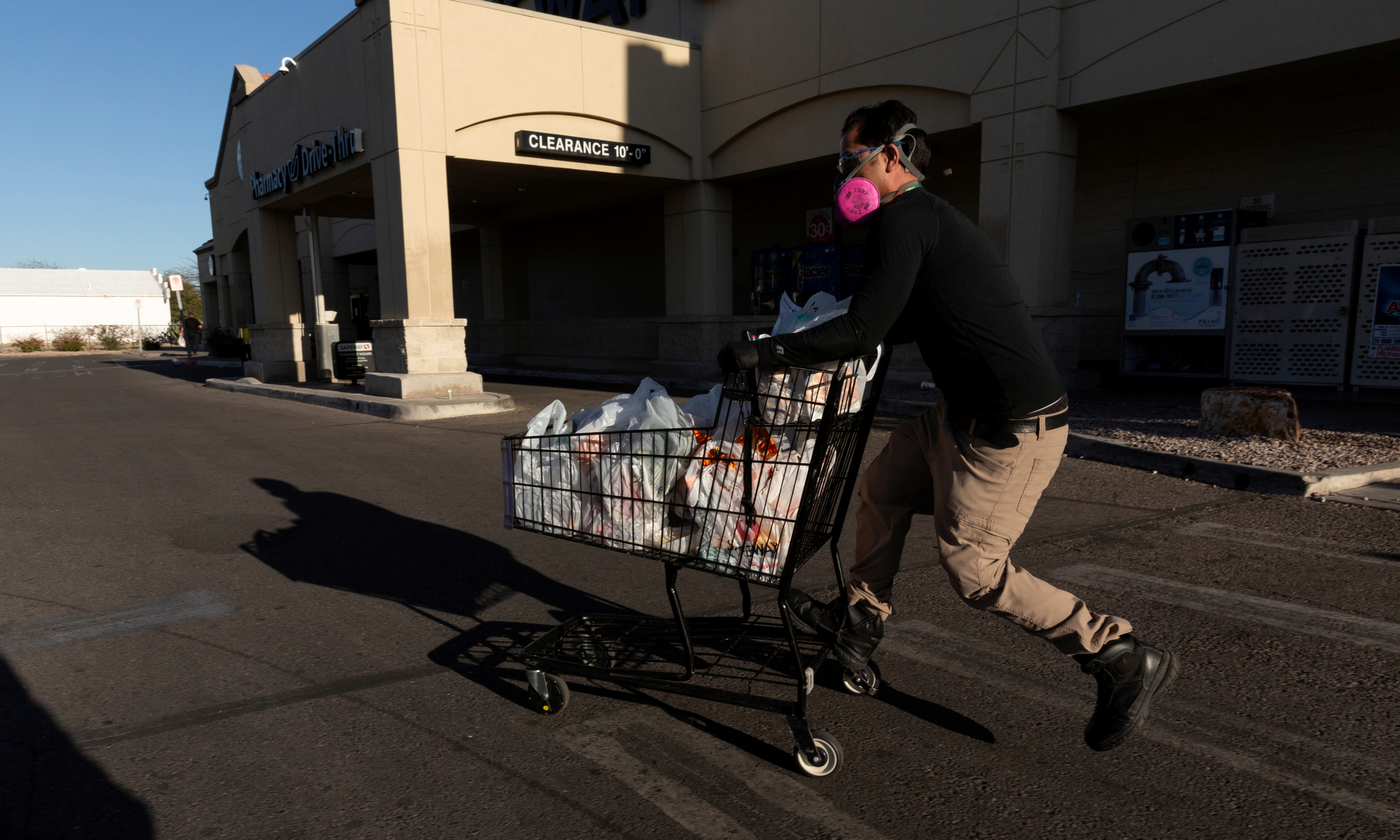 Instacart employee Eric Cohn, 34, heads to his car outside a Safeway grocery store while wearing a respirator mask