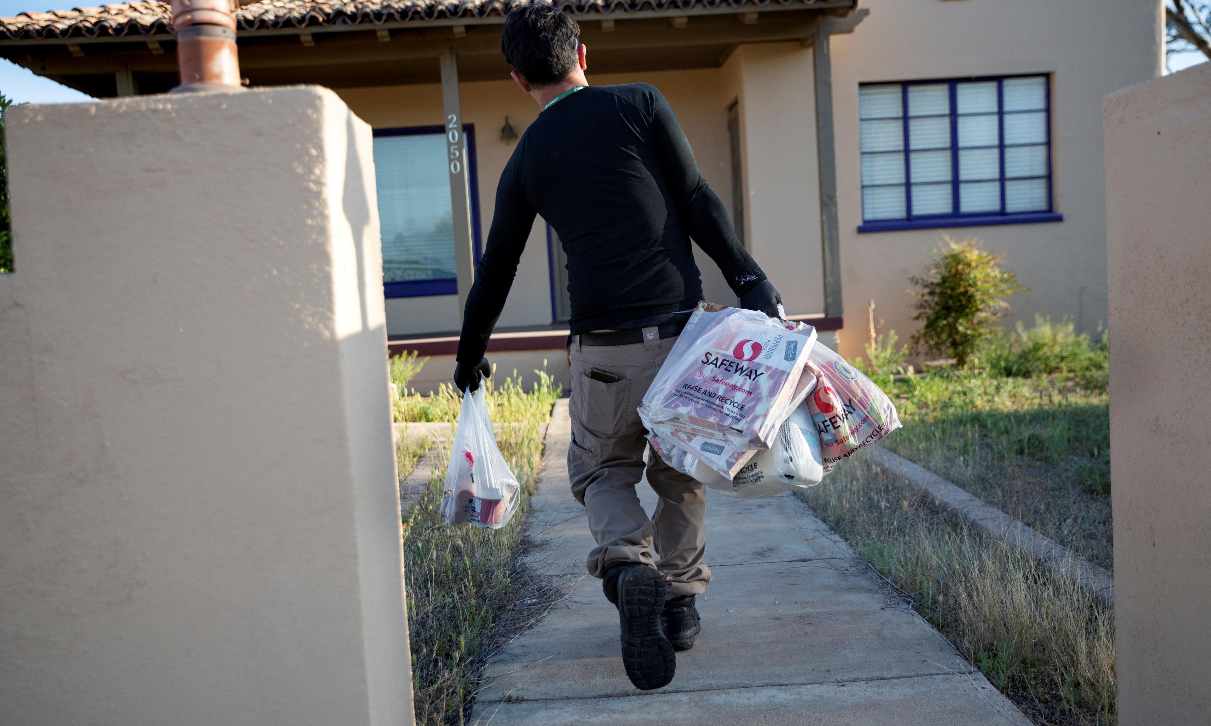 Instacart employee Eric Cohn, 34, delivers groceries to a residence while wearing a respirator mask.
