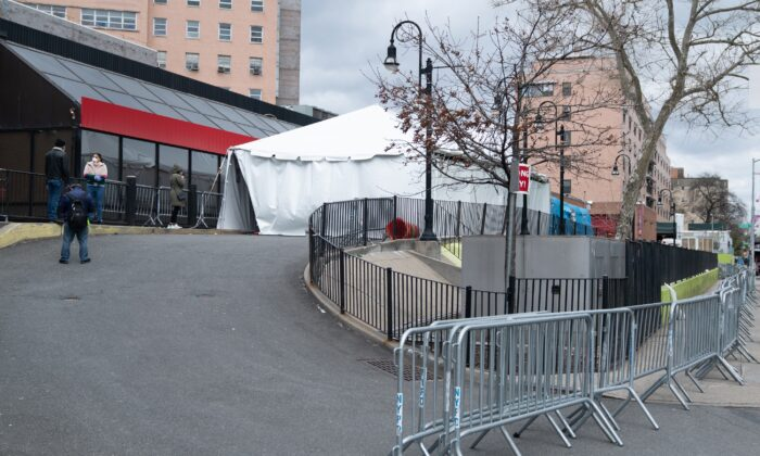 People stand in line while practicing social distancing as they wait to be processed through the triage tent outside of the emergency room at Elmhurst Medical Center in New York City on April 10, 2020. (David Dee Delgado/Getty Images)