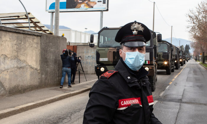 A Carabinieri officer blocks the road traffic as a convoy of military vehicles arrives at the Monumental Cemetery in Bergamo near Milan, Italy, on March 26, 2020. (Emanuele Cremaschi/Getty Images)