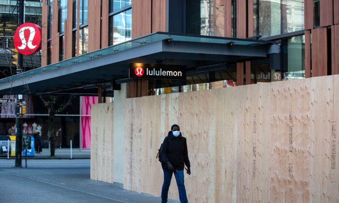 A woman walks past a boarded-up Lululemon store that has been closed due to the COVID-19 pandemic, in Vancouver on March 25, 2020. (The Canadian Press/Darryl Dyck)