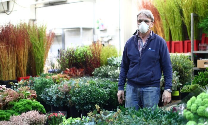 Gardener Herbert Jedletzberger wears a protective mask as he waits for customers at the central flower market (Grossgruenmarkt) during the partial reopening of stores after the Austrian government loosens its lockdown restrictions during the CCP virus outbreak in Vienna on April 14, 2020. (Lisi Niesner/Reuters)