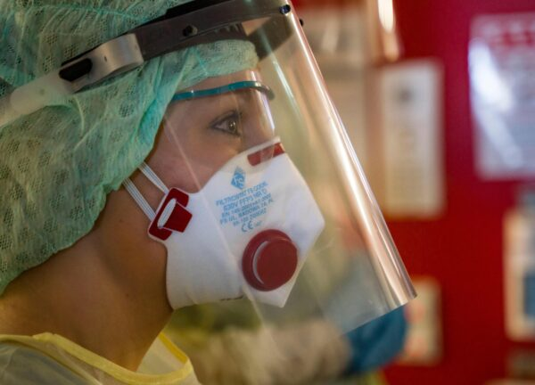 Nurse Lena Mueller wears a face mask and protective clothing