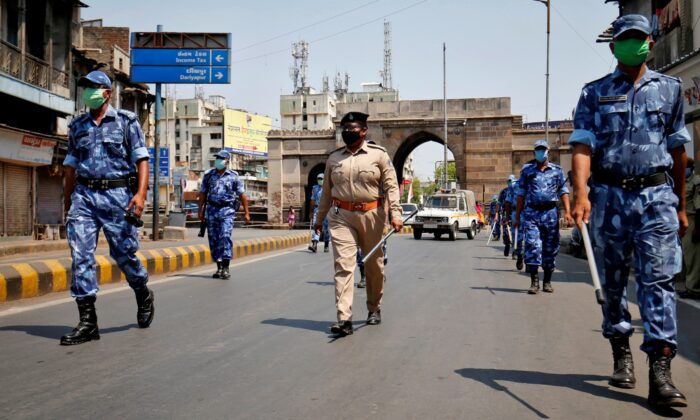Members of Rapid Action Force (RAF) patrol an empty street after India extended a nationwide lockdown to slow the spreading of the CCP virus in Ahmedabad, India on April 14, 2020. (Amit Dave/Reuters)