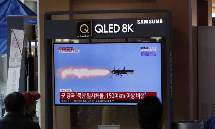 People watch a TV screen showing a news program reporting about North Korea's missiles with a file image at the Seoul Railway Station in Seoul on April 14, 2020. (Lee Jin-man/AP Photo)