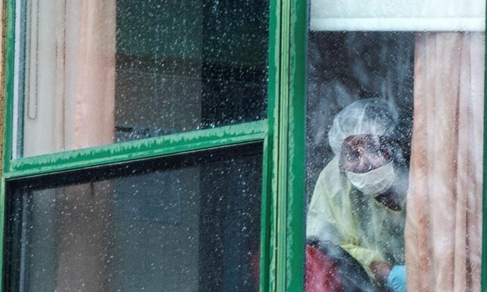 A person wearing protective equipment looks out of a window at the Herron seniors residence on April 13, 2020 in Dorval near Montreal's Trudeau airport. Thirty-one residents are confirmed to have died in the past month. (The Canadian Press/Ryan Remiorz)
