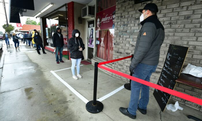Observing social distancing guidelines, a shop owner meets customers standing in line in Whittier, California, on April 9, 2020. (Frederic J. Brown/AFP/Getty Images)