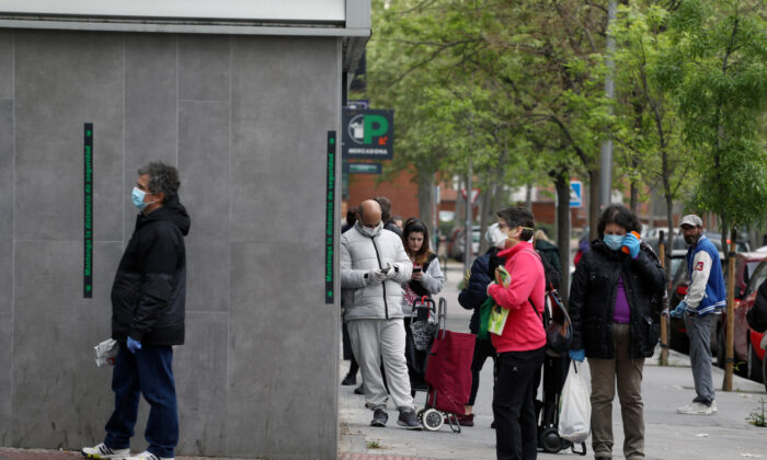 People keep social distance as they wait to enter a supermarket amid the CCP virus (COVID-19) outbreak in Madrid, Spain on April 14, 2020. (Sergio Perez/Reuters)