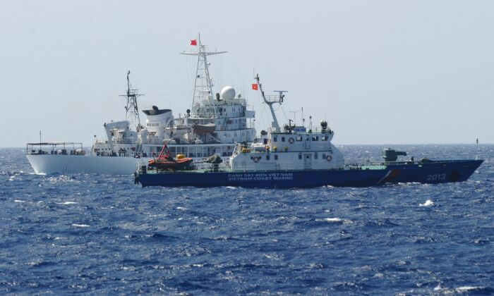 A Chinese coast guard ship (back) sails next to a Vietnamese coast guard vessel (front) near China's oil drilling rig in disputed waters in the South China Sea on May 14, 2014. (Hoang Dinh Nam/AFP via Getty Images)