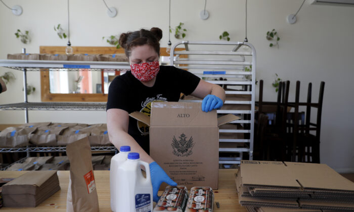 Monica Mileur packs grocery items into a box at Union Loafers restaurant Friday, April 10, 2020, in St. Louis. (Jeff Roberson/AP)