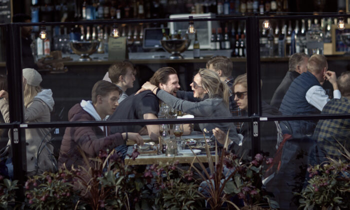A couple hug and laugh as they have lunch in a restaurant in Stockholm, Sweden on April 4, 2020. (Andres Kudacki/AP)