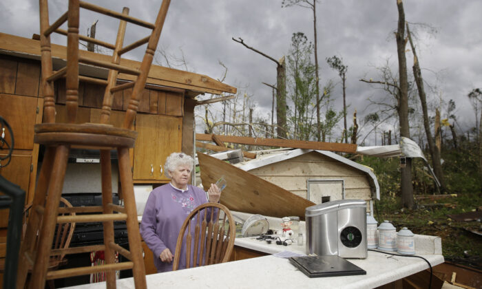 Emma Pritchett, 78, hold up a broken glass from her kitchen sink the day after a tornado hit on April 13, 2020, in Chatsworth, Ga. (Brynn Anderson/AP)