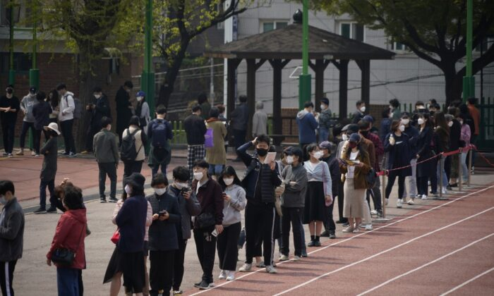 Voters wearing face masks in an effort to prevent the spread of COVID-19 wait in line to cast their ballots at a polling station during the parliamentary election in Seoul, South Korea, on April 15, 2020. (Kim Hong-Ji/Reuters)