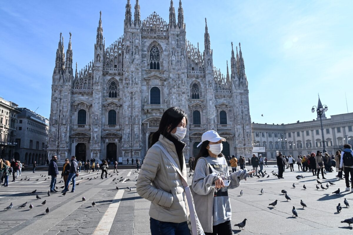 Two women wearing a protective facemask walk across the Piazza del Duomo, in front of the Duomo,